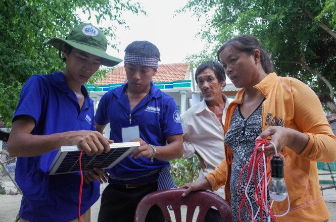 Sinh viên tình nguyÇn xem l¡i các thi¿t bË tr°Ûc khi l¯p ·t cho gia ình bà NguyÅn ThË Em. ¢nh: HUYÀN TRANG